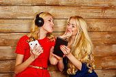 foto of sisters  - Two sisters blonde listening to music on headphones - JPG