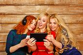 stock photo of three sisters  - Three sisters blond and red listening to music on headphones - JPG