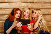 foto of three sisters  - Three sisters blond and red listening to music on headphones - JPG