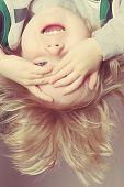 stock photo of peek  - Upside down toddler boy playing peek a boo - JPG