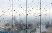 stock photo of raindrops  - Raindrops on glass window overlooking the City on background - JPG