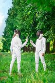 picture of rapier  - Two fencers women staying in park with crossed rapiers getting ready for competition - JPG