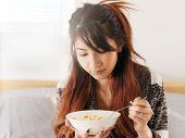 foto of noodles  - asian teen girl eating chicken noodle soup - JPG