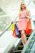 picture of escalator  - Beautiful young woman standing on escalator and carrying shopping bags - JPG