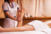 image of therapist massage  - Top view of massage therapist massaging beautiful female leg - JPG