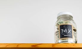 stock photo of irs  - Single glass jar with chalk labels used for saving US dollar bills and notes for tax and taxes - JPG