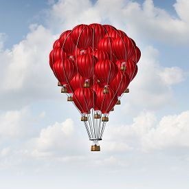 stock photo of joining  - Group concept as a team of red hot air balloons joined together as a symbol for teamwork unity and collaboration solidarity with people being lead by an individual manager - JPG