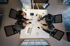 stock photo of gathering  - Office workers gather around a table to do research and implement new ideas - JPG