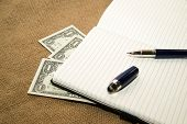 stock photo of memento  - Opened notebook with a blank sheet pen and money on the old tissue - JPG