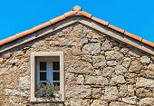 picture of stone house  - Old living house facade fragment stone wall with window under red tile roof Corsica France - JPG