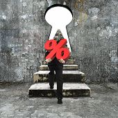 stock photo of keyhole  - Man carrying percentage sign climbing old concrete stairs toward keyhole with blank white view - JPG