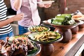 pic of buffet  - Asian woman and man choosing food at Indonesian buffet in restaurant - JPG