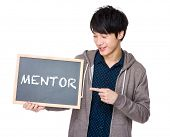 stock photo of mentoring  - Young man finger point to chalkboard showing a word mentor - JPG