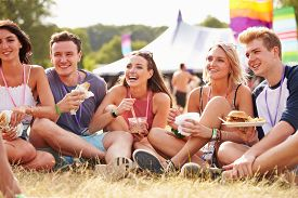 stock photo of eat grass  - Friends sitting on the grass eating at a music festival - JPG