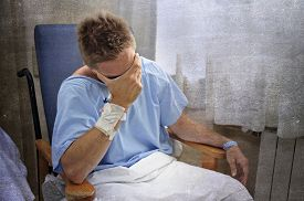 stock photo of medical condition  - young injured man crying in hospital room sitting alone in pain looking negative and worried for his bad health condition sitting on chair suffering depression on a grunge medical background - JPG