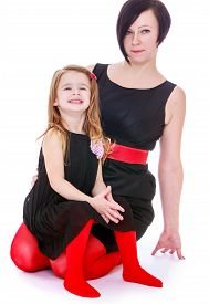 stock photo of tight dress  - Beautiful young mother with long bangs on the head and a black dress posing for the camera together with her small daughter who wears exactly the same clothes as mom - JPG