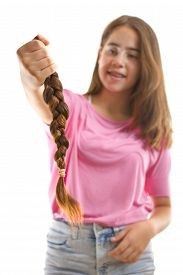 pic of generous  - Teenage girl in pink donating her hair to cancer patients - holding her former ponytail after a haircut generously donating her long hair for making wigs for cancer patients who lost their hair  ** Note: Shallow depth of field - JPG
