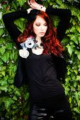 red hair fashion woman in black with fashion accessories agains wall with green rambler plant