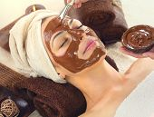 Chocolate Luxury Spa. Facial Mask. Beautiful young woman relaxing in beauty spa salon, applying choc poster