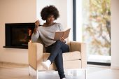 african american woman drinking cup of coffee reading book at fireplace. Young black girl with hot b poster