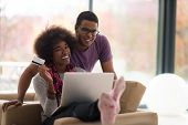 Happy young african american couple shopping online through laptop using credit card at home poster