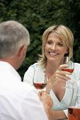 Couple talking, drinking wine outdoors