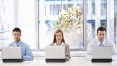 Young attractive businesspeople working on laptops individually in bright meeting room.?