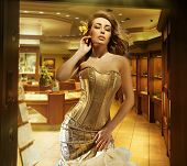 Cute blonde lady wearing golden dress in a jewelry shop