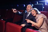 stock photo of comedy  - Young couple in cinema movie theater laughing while watching comedy show - JPG