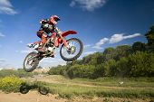 foto of dirt-bike  - red motocross rider in the air (with shadow)