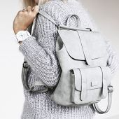 Unrecognizable model wearing casual outfit and holding leather backpack. Gray clothing in trendy min poster
