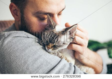 poster of Cat And Man, Portrait Of Happy Cat With Close Eyes And Young Beard Man. Handsome Young Man Is Huggin