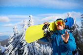 Smiling Snowboarder Posing Carrying Snowboard On Shoulders At Ski Resort Near Forest Before Freeride poster