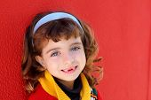 front teeth indented little girl smiling on a red wall background