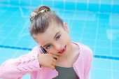 child little indented girl talking mobile phone in swimming pool