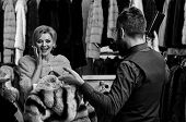 Shop Assistant With Beard Shows Fur Coat To Lady. Woman With Smiling Face In Fashion Store. Couple I poster