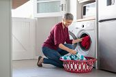 Happy senior woman loading dirty clothes in washing machine. Smiling mature woman sitting on floor p poster
