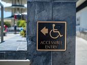 Gold And Black Accessible Entry Sign Posting With Wheelchair Handicap Logo And Arrow Pointing To Lef poster