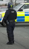 stock photo of truncheon  - Uk police officer in full riot gear at the scene of a public disturbance with a police car blurred in the background - JPG