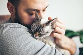 Cat And Man, Portrait Of Happy Cat With Close Eyes And Young Beard Man. Handsome Young Man Is Huggin poster