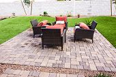 Four Wicker Chairs With Pillows On Brick Yard Patio poster