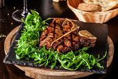 The Concept Of Italian Cuisine. Juicy T-bone Steak Of Beef Aging Stewed Meat, With Rucola Salad And poster