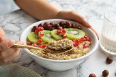 Woman Eating Quinoa Porridge With Hazelnuts, Kiwi And Pomegranate Seeds At Marble Table, Closeup poster