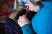 Old Poor Gray Hair Woman Holds Ukrainian Paper Money In Her Hands. Woman Is Sad. Poor Life In Villag poster