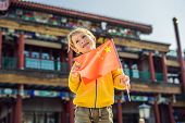 Enjoying Vacation In China. Young Boy With National Chinese Flag On The Background Of The Old Chines poster