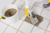Trabalhador com espátula repara antigos azulejos brancos com adesivo da telha