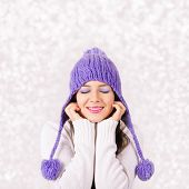 Happy young woman with purple hat enjoying the snow