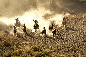 Three Cowboys Rounding Up Horses