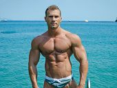 Handsome Young Bodybuilder Standing With Sea Or Ocean Behind
