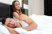 pic of grieving  - Attractive woman grieves while her husband is sleeping at home - JPG